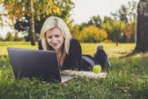 Student girl with laptop studying in park — Stock Photo