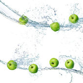 Green apples in splash of water isolated — Stock Photo