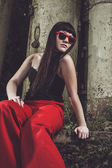 Stylish girl in red pants and glasses — Stock Photo