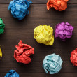 Crumpled colorful paper on wooden background — Stock Photo #48763775
