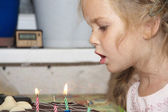 Girl blows out candles — Stock Photo