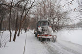 Snow-removal tractor cleans alley in the park — Stock Photo