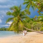 Happy couple sitting on the sunny beach — Stock Photo