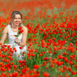 Beatiful woman in field of bright red poppy flowers in summer — Stock Photo