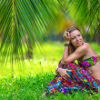 Beautiful girl under a palm tree — Stock Photo