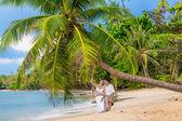 Feliz pareja sentada en la playa soleada — Foto de Stock