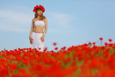 Beauty woman in poppy field in white dress — Stock Photo