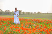 Girl in a white dress in the poppy field — Stock Photo