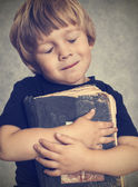 Little boy hugging an old book — Stockfoto