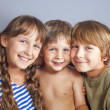Cute sister hugging younger brothers — Stock Photo