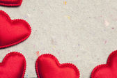 Red hearts on vintage paper background — Stockfoto