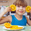 Boy eats orange — Stock Photo