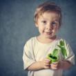 Portrait of funny little boy with window plants — Stock Photo