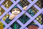 Little baby boy  looking through blue fence — Stock Photo