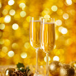 Two glasses of champagne with a Christmas decor in the background — Stok fotoğraf