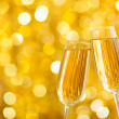 Two glasses of champagne with lights in the background. Very shallow depth of field. — Stock Photo