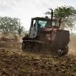 Agricultural tractor cultivating land — Stock Photo #41307837