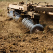 Stock Photo: Part ot agricultural tractor cultivating land
