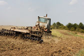 Agricultural tractor cultivating land — Stock Photo