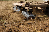 Part ot agricultural tractor cultivating land  — Stock Photo