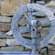 Retro Spinning Wheel Against Stone Wall Background - Stock Photo