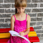 Girl draws on the album sitting bench — Stock Photo