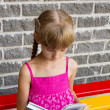 Stock Photo: Girl reading book on bench 5049