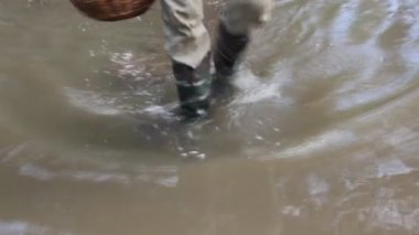 Man in rubber boots walks on water — Stock Video