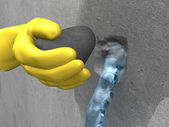Yellow-gloved hand put the plug (extra-rapid cement) in the hole — Stock Photo