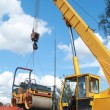 Stock Photo: Loading compactor on transportation machine using crane