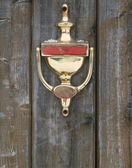Golden doorknocker on a wood door — Stock Photo