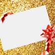 Christmas sheet of paper with bow and ribbons on yellow defocused background — Stock Photo