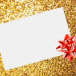 Stock Photo: Christmas sheet of paper with bow and ribbons on yellow defocused background