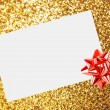 Christmas sheet of paper with bow and ribbons on yellow defocused background — Stock Photo #15434803