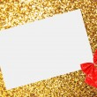Christmas sheet of paper with bow and ribbons on yellow defocused background — Stock Photo #15434805