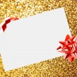 Christmas sheet of paper with bow and ribbons on yellow defocused background — Stock Photo #15434807