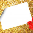 Christmas sheet of paper with bow and ribbons on yellow defocused background — Stock Photo #15434821