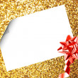 Royalty-Free Stock Photo: Christmas sheet of paper with bow and ribbons on yellow defocused background