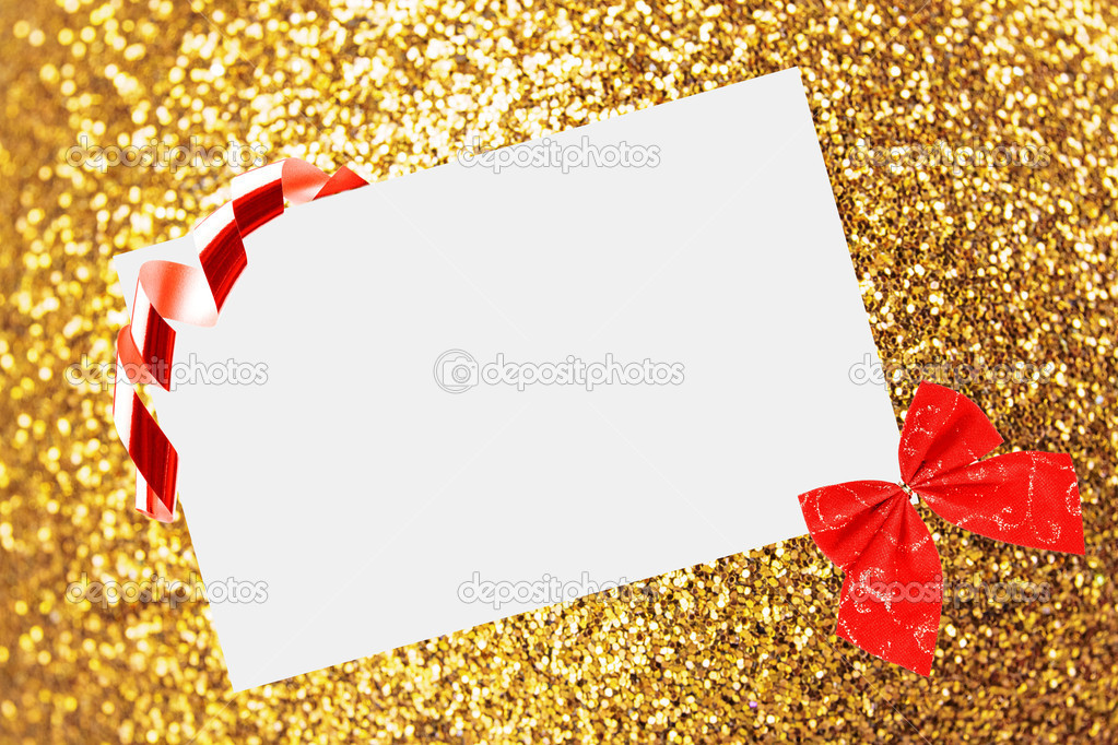 Christmas sheet of paper with bow and ribbons on yellow defocused background  Stock Photo #15434799