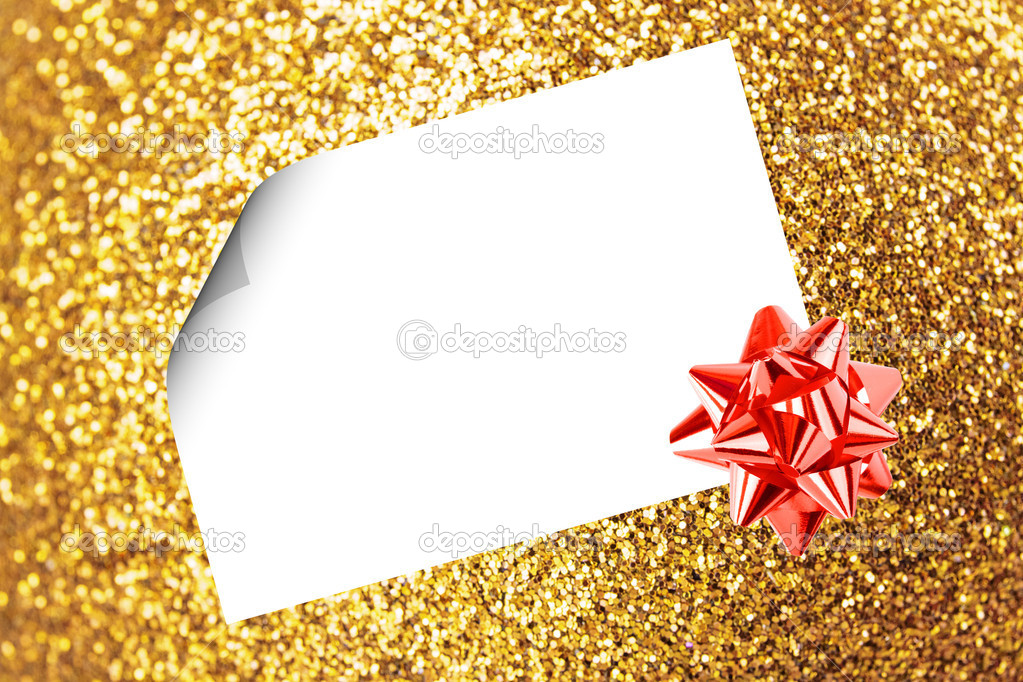 Christmas sheet of paper with bow and ribbons on yellow defocused background — Stock Photo #15434829