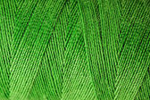 Macro view of green thread wound on a spool — Stock Photo