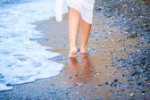 Young woman walking on a beach — Stock Photo
