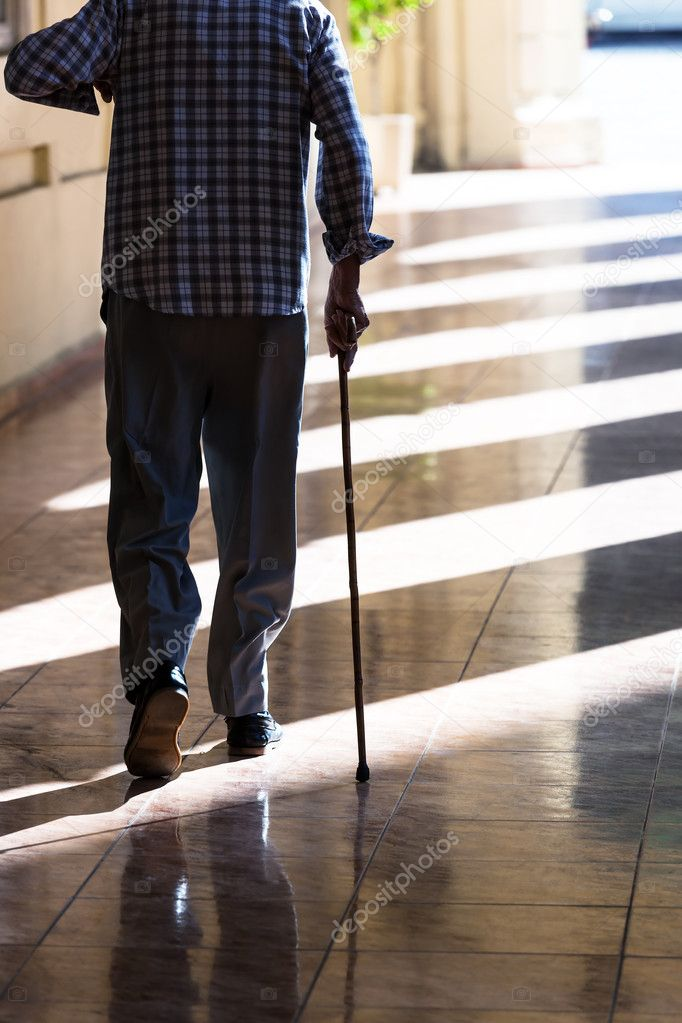 An old man with a cane on the sidewalk — Stock Photo #19475625