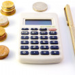 Calculator, coins and pen — Stock Photo