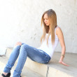 Outdoor photo of pretty teenage girl sitting - Stock Photo