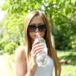 Profile of beautiful woman drink some water from plastic bottle — Stock Photo
