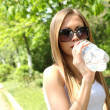 Beautiful woman drinking water at summer green park. — Stock Photo #12448040