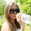 Beautiful woman drinking water at summer green park. — Stock Photo