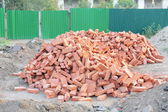 Lots red clay bricks lying — Stock Photo