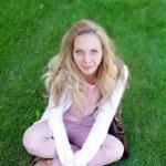 güzel genç gülümseyen kadın portresi çimlerde oturuyor — Stok fotoğraf